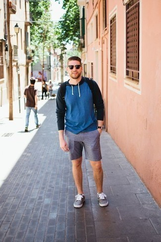 Combinar una sudadera con capucha azul: Elige una sudadera con capucha azul y unos pantalones cortos azules para un look diario sin parecer demasiado arreglada. Tenis de lona grises son una opción buena para completar este atuendo.