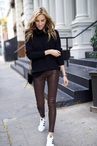 Cómo combinar: bolso bandolera de ante negro, tenis de cuero blancos, pantalones pitillo de cuero en marrón oscuro, jersey de cuello alto negro