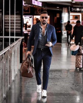 Cómo combinar: bolsa de viaje de cuero marrón, tenis de cuero blancos, traje azul marino, chaqueta vaquera azul