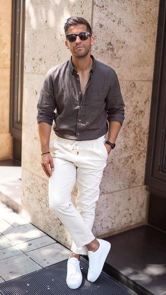 Outfits hombres en clima caliente: Para crear una apariencia para un almuerzo con amigos en el fin de semana utiliza una camisa de manga larga de lino en marrón oscuro y unos vaqueros blancos. Tenis blancos son una opción práctica para completar este atuendo.