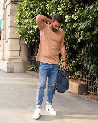 Cómo combinar: mochila de lona azul marino, tenis de cuero blancos, vaqueros azules, camiseta con cuello circular marrón claro