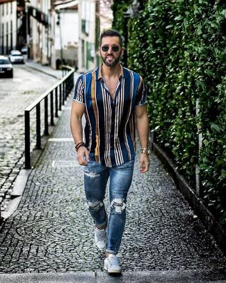 Cómo combinar: gafas de sol negras, tenis blancos, vaqueros pitillo desgastados azules, camisa de manga corta de rayas verticales azul marino