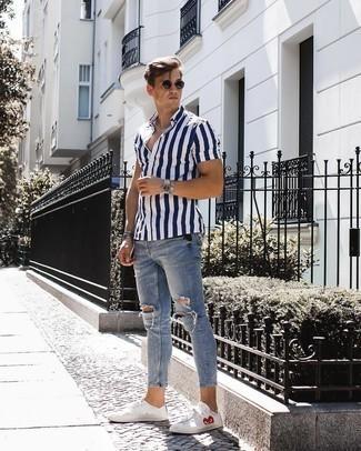 Outfits hombres estilo relajado: Utiliza una camisa de manga corta de rayas verticales en azul marino y blanco y unos vaqueros pitillo desgastados celestes para un look agradable de fin de semana. ¿Te sientes valiente? Opta por un par de tenis estampados blancos.