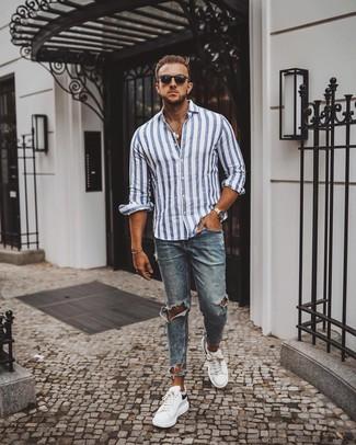 Cómo combinar: gafas de sol negras, tenis de cuero en blanco y negro, vaqueros pitillo desgastados azules, camisa de manga larga de rayas verticales en blanco y azul