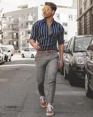 Cómo combinar: correa de cuero marrón claro, tenis de ante en tabaco, vaqueros pitillo grises, camisa de vestir de rayas verticales en azul marino y blanco