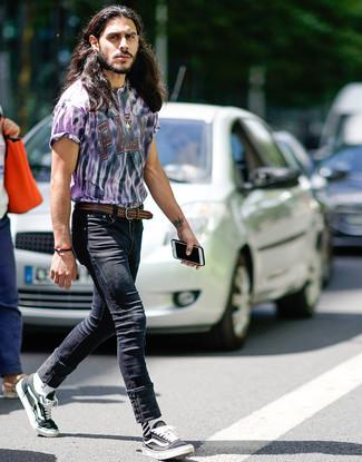 Cómo combinar: correa de cuero tejida marrón, tenis de lona en negro y blanco, vaqueros pitillo negros, camiseta con cuello circular efecto teñido anudado violeta claro