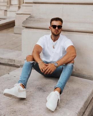 Outfits hombres en clima caliente: Para un atuendo tan cómodo como tu sillón elige una camiseta con cuello circular blanca y unos vaqueros pitillo desgastados azules. Dale un toque de elegancia a tu atuendo con un par de tenis de cuero blancos.