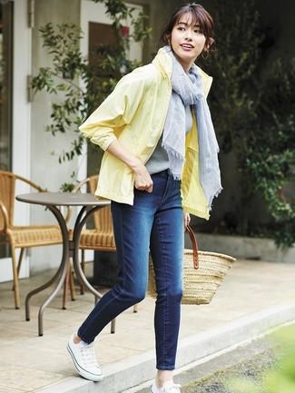 Cómo combinar: bolsa tote de paja marrón claro, tenis de lona blancos, vaqueros pitillo azul marino, chubasquero amarillo