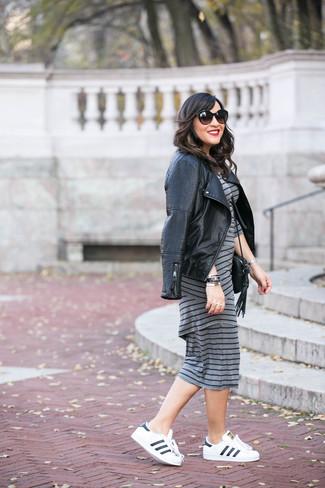 Cómo combinar: bolso bandolera de cuero negro, tenis de cuero en blanco y negro, vestido ajustado de rayas horizontales gris, chaqueta motera de cuero acolchada negra