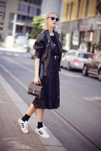 Cómo combinar: bolso de hombre de cuero negro, tenis de cuero en blanco y negro, vestido midi de encaje negro, chaqueta motera de cuero negra