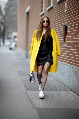 Cómo combinar: cartera de cuero plateada, tenis blancos, vestido tubo de satén negro, abrigo amarillo