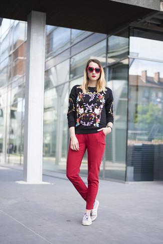 Cómo combinar: gafas de sol en rojo y negro, tenis violeta claro, pantalones pitillo rojos, jersey con cuello circular bordado negro