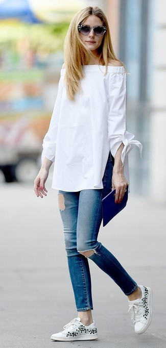 Look de Olivia Palermo: Top Con Hombros Descubiertos Blanco, Vaqueros Pitillo Desgastados Azules, Tenis con print de flores Blancos, Cartera Sobre de Cuero Azul