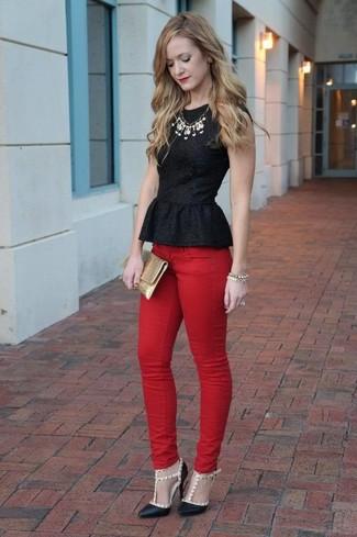 Cómo combinar: top con sobrefalda negro, vaqueros pitillo rojos, zapatos de tacón de cuero con tachuelas negros, cartera sobre de cuero dorada