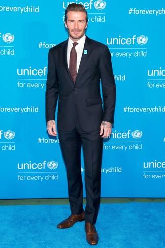 Look de David Beckham: Traje de rayas verticales azul marino, Camisa de vestir blanca, Zapatos oxford de cuero marrónes, Corbata de paisley burdeos