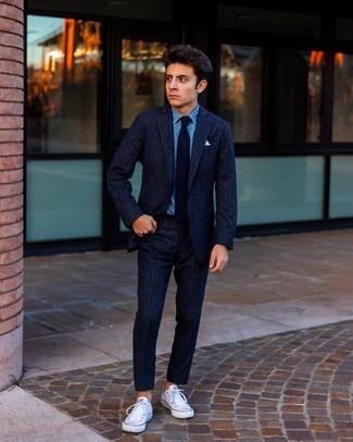 Cómo combinar: traje de lana de rayas verticales azul marino, camisa vaquera azul, tenis de lona blancos, corbata negra