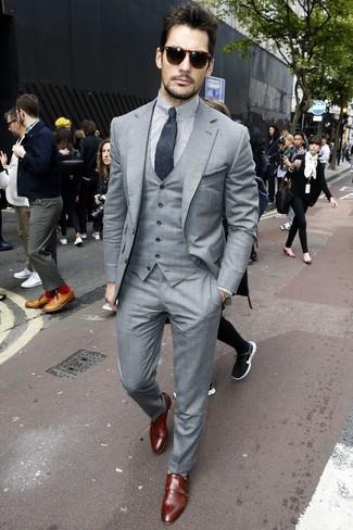 Look de David Gandy: Traje de Tres Piezas Gris, Camisa de Vestir de Rayas Verticales en Blanco y Negro, Zapatos con Doble Hebilla de Cuero en Marrón Oscuro, Corbata en Gris Oscuro