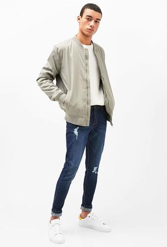 Cómo combinar: tenis de cuero blancos, vaqueros desgastados azul marino, jersey con cuello circular blanco, cazadora de aviador gris