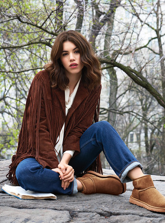 Cómo combinar: botas ugg marrónes, vaqueros azules, blusa de botones blanca, chaqueta abierta de ante сon flecos en marrón oscuro