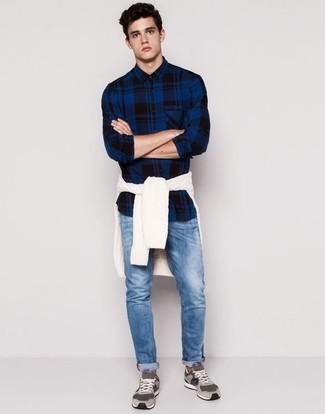 Cómo combinar: tenis de ante grises, vaqueros azules, camisa de manga larga de tartán azul marino, jersey de ochos blanco