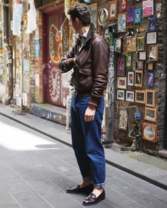 Cómo combinar: mocasín de cuero morado oscuro, vaqueros azules, camisa de manga larga celeste, cazadora de aviador de cuero en marrón oscuro
