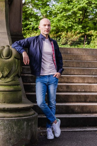 Cómo combinar: tenis de cuero blancos, vaqueros azules, camiseta con cuello circular en beige, cazadora harrington azul marino