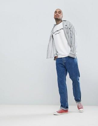 Cómo combinar: tenis de lona rojos, vaqueros azules, camiseta con cuello circular estampada en blanco y negro, camisa de manga larga de rayas verticales en blanco y negro
