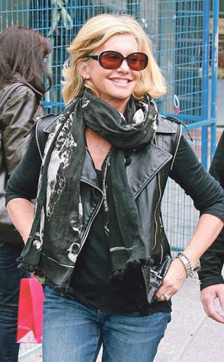 Cómo combinar: bufanda estampada negra, vaqueros azules, camiseta sin manga negra, chaqueta motera de cuero negra