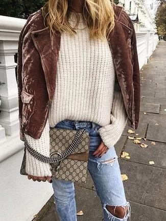 Cómo combinar: bolso bandolera de cuero estampado marrón, vaqueros desgastados azules, jersey oversized de punto en beige, chaqueta motera de ante marrón
