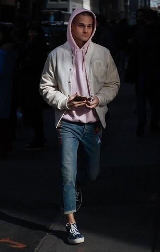 Combinar una chaqueta varsity en beige: Para crear una apariencia para un almuerzo con amigos en el fin de semana equípate una chaqueta varsity en beige junto a unos vaqueros bordados azules. ¿Quieres elegir un zapato informal? Elige un par de zapatillas altas de lona estampadas azul marino para el día.