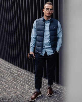 Cómo combinar: zapatos brogue de cuero marrónes, vaqueros de pana azul marino, camisa de manga larga celeste, chaleco de abrigo azul marino
