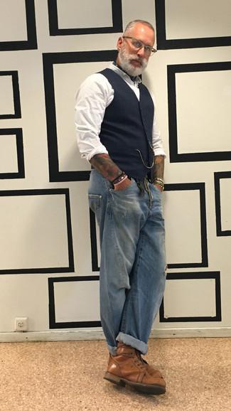 Moda para hombres de 40 años: Intenta ponerse un chaleco de vestir de tartán azul marino y unos vaqueros desgastados azules para un almuerzo en domingo con amigos. Opta por un par de botas casual de cuero marrónes para mostrar tu inteligencia sartorial.