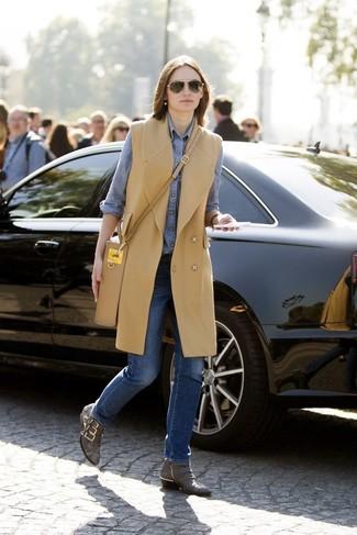 Cómo combinar: botines de cuero con print de serpiente grises, vaqueros azules, camisa de vestir de cambray azul, abrigo sin mangas marrón claro