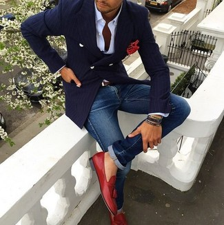 Cómo combinar: mocasín con borlas de cuero rojo, vaqueros azules, camisa de vestir blanca, blazer cruzado de rayas verticales azul marino