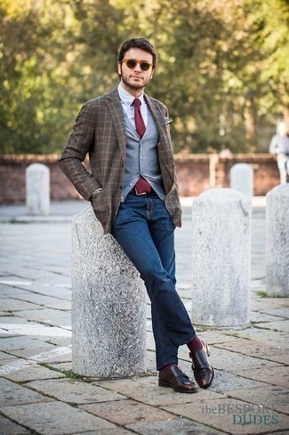 Combinar unos zapatos con doble hebilla de cuero en marrón oscuro: Considera emparejar un chaleco de punto gris junto a unos vaqueros azul marino para lograr un look de vestir pero no muy formal. ¿Te sientes valiente? Usa un par de zapatos con doble hebilla de cuero en marrón oscuro.