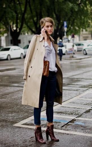 Cómo combinar: botines de cuero burdeos, vaqueros azul marino, camisa de vestir blanca, gabardina en beige