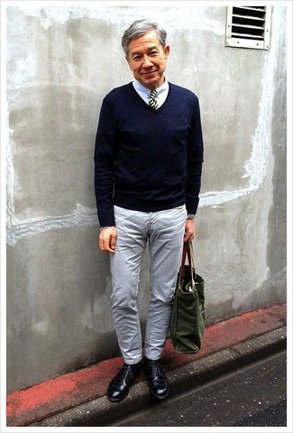 Cómo combinar: zapatos derby de cuero negros, vaqueros grises, camisa de vestir blanca, jersey de pico azul marino
