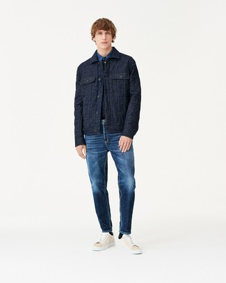 Cómo combinar: tenis de cuero en beige, vaqueros azul marino, camisa vaquera azul, chaqueta estilo camisa acolchada azul marino