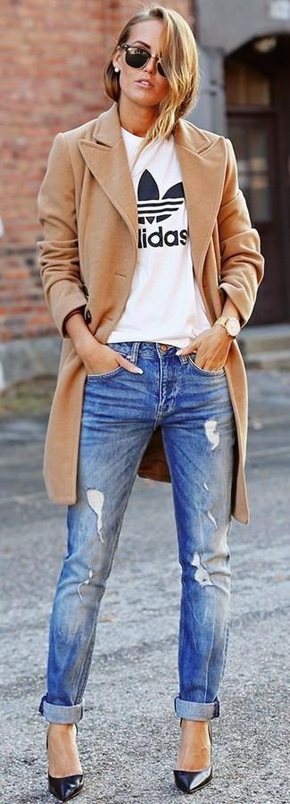 Cómo combinar: zapatos de tacón de cuero negros, vaqueros desgastados azules, camiseta con cuello circular estampada en blanco y negro, abrigo marrón claro