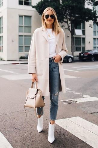 Cómo combinar: botines de cuero blancos, vaqueros desgastados azules, camiseta con cuello circular blanca, abrigo en beige