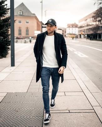 Outfits hombres en clima fresco: Un abrigo largo negro y unos vaqueros azules son un look perfecto para ir a la moda y a la vez clásica. Haz este look más informal con tenis de lona en negro y blanco.