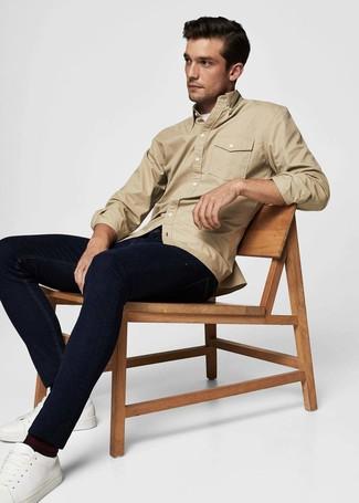 Cómo combinar: tenis de cuero blancos, vaqueros azul marino, camiseta con cuello circular blanca, chaqueta estilo camisa marrón claro