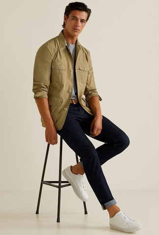 Cómo combinar: tenis de lona blancos, vaqueros azul marino, camiseta con cuello circular gris, chaqueta estilo camisa verde oliva