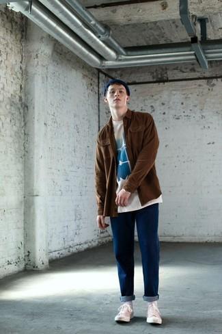 Cómo combinar: tenis de lona blancos, vaqueros azules, camiseta con cuello circular estampada en blanco y azul, chaqueta estilo camisa marrón