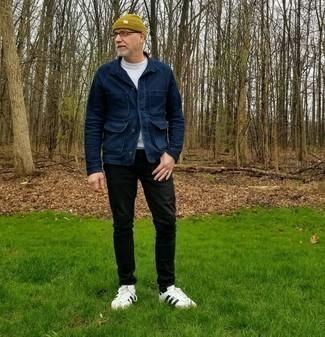 Moda para hombres de 50 años: Empareja una chaqueta estilo camisa azul marino con unos vaqueros negros para conseguir una apariencia relajada pero elegante. Si no quieres vestir totalmente formal, completa tu atuendo con tenis de cuero en blanco y negro.