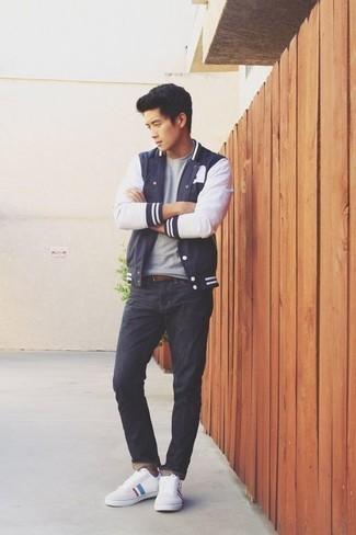 Combinar una correa de cuero marrón: Empareja una chaqueta varsity en azul marino y blanco con una correa de cuero marrón para un look agradable de fin de semana. Con el calzado, sé más clásico y complementa tu atuendo con tenis de lona estampados blancos.