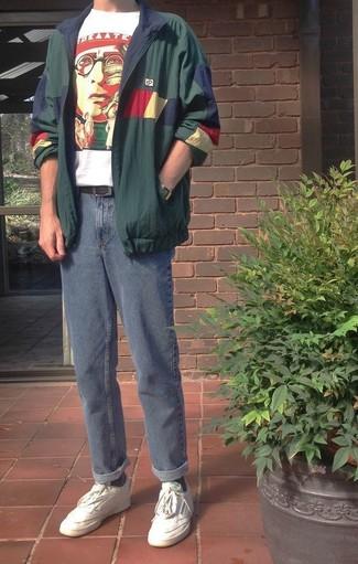 Cómo combinar: tenis de cuero blancos, vaqueros azules, camiseta con cuello circular estampada en blanco y rojo, chubasquero verde oscuro
