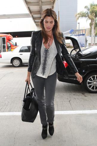 Cómo combinar: botines de ante negros, vaqueros grises, camiseta con cuello en v con print de serpiente gris, blazer de cuero negro