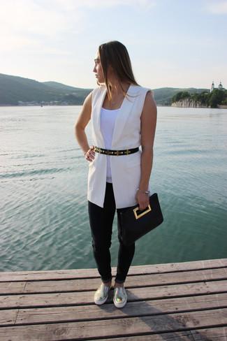 Cómo combinar: zapatillas slip-on de cuero doradas, vaqueros negros, camiseta sin manga blanca, blazer sin mangas blanco
