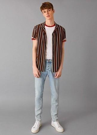 Outfits hombres en verano 2020: Elige una camisa de manga corta de rayas verticales marrón y unos vaqueros celestes para lidiar sin esfuerzo con lo que sea que te traiga el día. Tenis de cuero blancos son una opción práctica para complementar tu atuendo. Es una idea excelente para llevarlo en jornadas en verano.